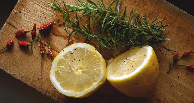 lemons on cutting boards with herbs