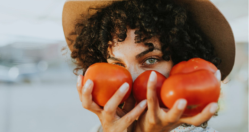 A woman holding two tomatoes